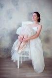 拿着手舞蹈的一位美丽的年轻芭蕾舞女演员的画象pointe鞋子 库存图片