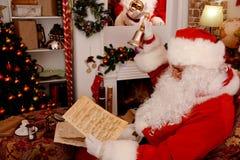 拿着手铃和音乐原稿,音乐纸张的圣诞老人 库存图片