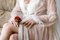 拿着扣眼的新娘 举行新郎的新娘的柔和的手钮扣眼上插的花 免版税库存照片