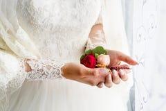 拿着扣眼的新娘 举行新郎的新娘的柔和的手钮扣眼上插的花 库存图片
