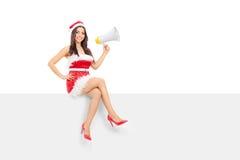 拿着扩音机的女性圣诞老人供以座位在盘区 图库摄影