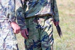拿着投掷的刀子的伪装的战士 图库摄影