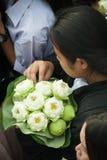 拿着投掷的妇女莲花入在磨擦Bua节日的小船 免版税库存图片