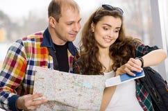 拿着护照和地图的男人和妇女 看时钟和研究的指南针方向 蜜月 库存图片