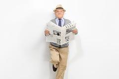 拿着报纸的资深绅士 免版税库存照片