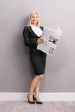 拿着报纸的年轻白肤金发的女实业家 免版税图库摄影