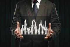 拿着抽象企业图表的商人 免版税库存照片