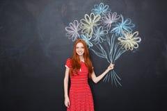 拿着拉长的花的花束在黑板背景的微笑的妇女 免版税库存图片