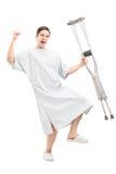 拿着拐杖的医院褂子的愉快的男性患者 免版税库存照片