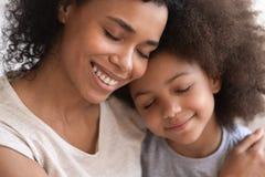 拿着拥抱的逗人喜爱的小孩女儿的爱恋的年轻非洲母亲 免版税库存图片
