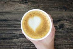 拿着拿铁咖啡用艺术在褐色的心脏牛奶的一个人 库存图片