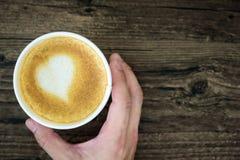 拿着拿铁咖啡用艺术在褐色的心脏牛奶的一个人 图库摄影