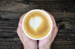 拿着拿铁咖啡用艺术心脏牛奶的一个人隔绝在褐色 库存图片