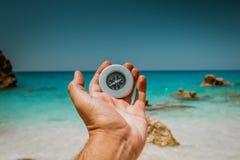 拿着指南针的手在海滩 库存图片