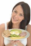 拿着挪威样式早餐的板材健康可爱的愉快的少妇 免版税图库摄影