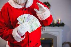拿着捆绑欧元的圣诞老人 免版税库存图片