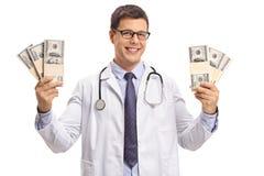 拿着捆绑金钱和微笑的医生 免版税库存照片