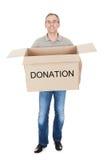 拿着捐赠箱子的愉快的人 免版税库存照片
