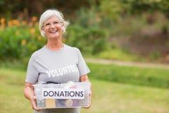 拿着捐赠箱子的愉快的祖母 免版税库存图片