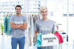 拿着捐赠箱子的金发碧眼的女人志愿者 免版税库存照片