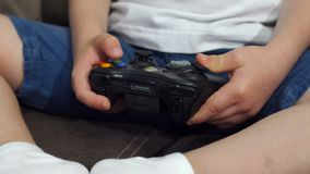 拿着控制杆和在家打电子游戏的一个小男孩的特写镜头 股票视频