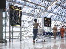 拿着推车的妇女在机场门搭乘飞行乘客 库存图片