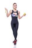 拿着措施磁带和绿色苹果的微小和健康少妇佩带的运动服田径服隔绝在白色背景 免版税库存图片