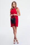 拿着提包的红色礼服的时尚妇女 免版税库存图片