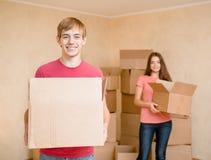 拿着搬入的年轻夫妇纸板箱一个新房 免版税库存照片