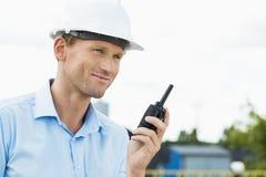 拿着携带无线电话的微笑的建筑师在建造场所 免版税库存照片