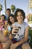 拿着摄象机的男孩(13-15)坐户外与姐妹(7-9)和父母画象。 免版税库存照片