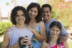 拿着摄象机的男孩(13-15)站立户外与姐妹(7-9)和父母画象。 库存图片