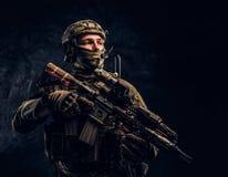 拿着攻击步枪的伪装制服的全副武装的战士 r 免版税库存图片