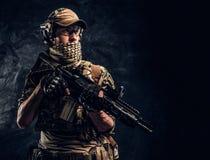 拿着攻击步枪的伪装制服的全副武装的战士 r 库存图片