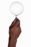 拿着放大镜的人的手 免版税库存照片