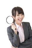 拿着放大镜的年轻亚裔女实业家 免版税图库摄影