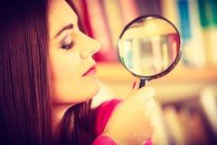 拿着放大镜的滑稽的女孩 图库摄影