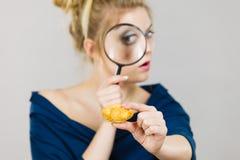 拿着放大镜调查的面包的妇女 免版税图库摄影