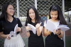 拿着教科书和笑激动幸福的亚裔少年站立室外 库存图片