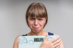 拿着数字式标度在帮助下的沮丧的超重妇女! 库存照片