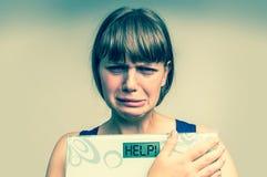 拿着数字式标度在帮助下的沮丧的超重妇女! 库存图片