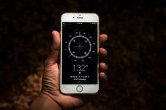 拿着数字式流动指南针的手 图库摄影