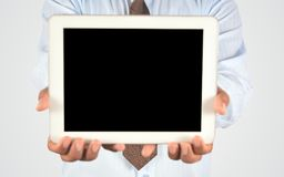 拿着数字式片剂个人计算机的商人 免版税库存图片