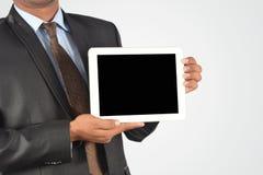 拿着数字式片剂个人计算机,被隔绝的非常professiona的商人 免版税库存图片