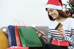 拿着数字式片剂和信用卡与ma的年轻亚裔妇女 库存图片