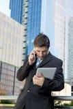 拿着数字式片剂和手机的繁忙的商人劳累了过度户外 免版税库存照片
