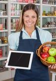 拿着数字式片剂和果子的女推销员 免版税库存照片