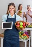 拿着数字式片剂和果子的女推销员 免版税库存图片