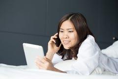 拿着数字式片剂和电话的年轻亚裔妇女 免版税库存图片