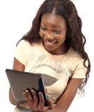 拿着数字式片剂的俏丽的微笑的妇女 免版税库存图片